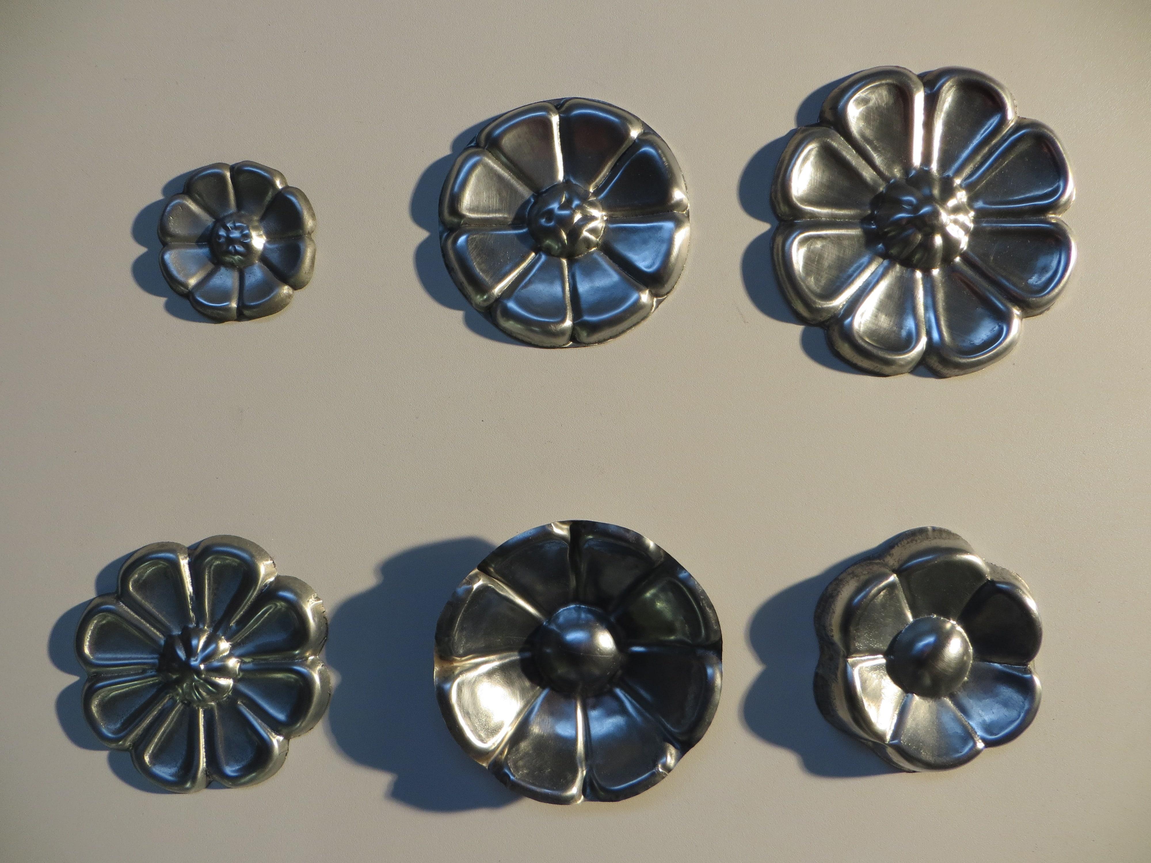 Rosaces estampées en Zinc naturel. En haut, de gauche à droite : Ref.R19 diam.80mm / Ref.R20 diam.120mm / Ref.R21 diam.150mm. En bas, de gauche à droite : Ref.R22 diam.125mm / Ref.R23 diam 125mm / Ref.R24 diam 115mm