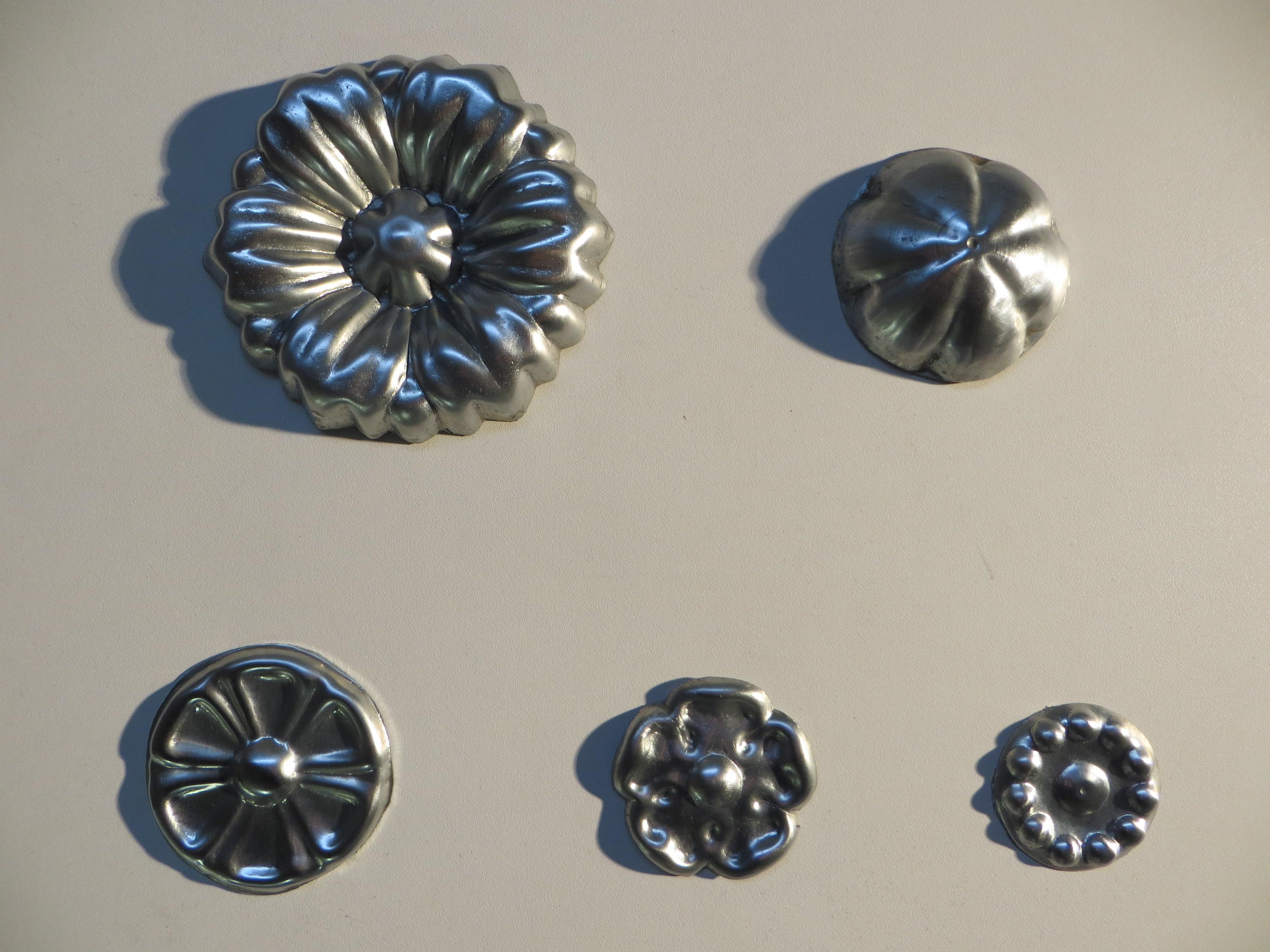 Rosaces estampées en Zinc naturel. En haut, de gauche à droite : Ref.R1 diam.135mm / Ref.R2 diam.80mm  En bas, de gauche à droite : Ref.R3 diam.80mm / Ref.R4 diam 70mm / Ref.R5 diam 55mm